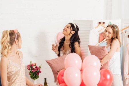 Foto de Hermosas chicas felizes multiétnicas en camisa de dormir celebrando con copas de champagne y globos en pijama party - Imagen libre de derechos