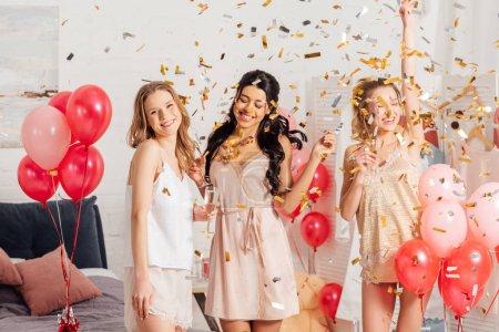 Foto de Hermosas chicas multiculturales felizes sosteniendo copas de champán y celebrando con confeti cayendo durante la fiesta de pijamas - Imagen libre de derechos
