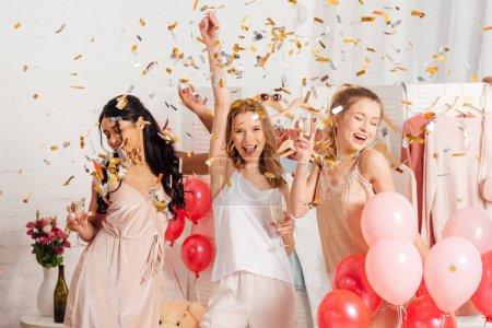 Photo pour Belles filles multiculturelles gaies tenant des verres de champagne et célébrant sous les confettis tombant pendant la soirée pyjama - image libre de droit