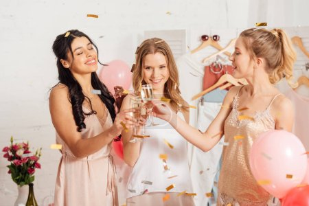 Photo for Beautiful multicultural girls clinking champagne glasses and celebrating under falling confetti during pajama party - Royalty Free Image