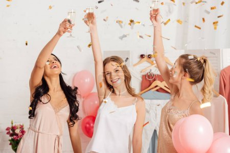 Photo for Beautiful multicultural girls toasting with champagne glasses and celebrating under falling confetti during pajama party - Royalty Free Image