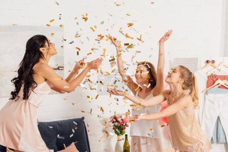 Photo for Beautiful multicultural girls in nightwear having fun under falling confetti during pajama party - Royalty Free Image