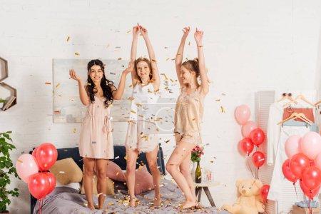 Foto de Hermosas chicas multiculturales en camisa de dormir bailando y divirtiendo en confeti cae durante fiesta de pijamas - Imagen libre de derechos