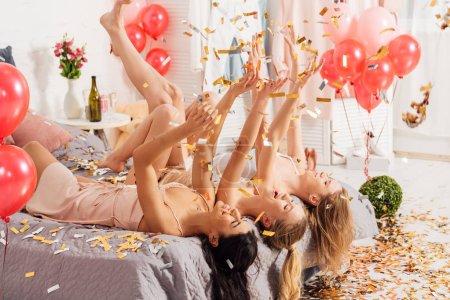 Foto de Hermosas chicas multiculturales felizes tumbado en la cama con confeti cayendo durante la fiesta de pijamas - Imagen libre de derechos