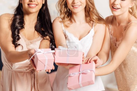 Photo for Cropped view of smiling multicultural girls in nightwear holding pink gift boxes - Royalty Free Image