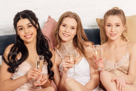 Photo for Beautiful smiling multicultural girls with champagne glasses in bed looking at camera during pajama party - Royalty Free Image