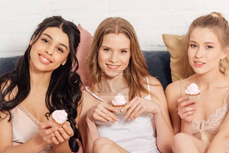 Photo for Beautiful smiling multicultural girls in nightwear looking at camera and holding cupcakes during pajama party - Royalty Free Image