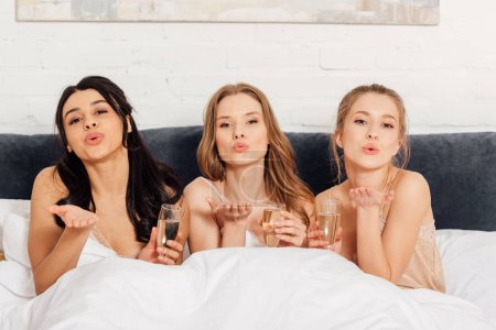 Photo for Beautiful multicultural girls with champagne glasses in bed looking at camera and blowing air kisses during pajama party - Royalty Free Image
