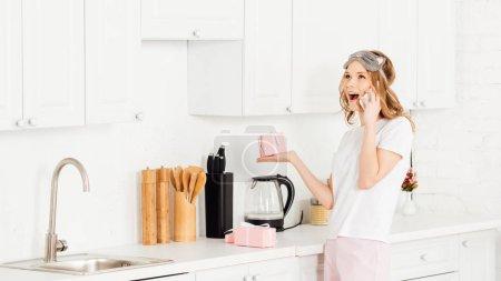 Photo pour Belle fille excitée en pyjama parler sur smartphone tout en maintenant la boîte-cadeau en cuisine - image libre de droit