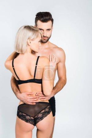 Photo pour Torse nu étreignant blonde séduisante copine copain isolée sur fond gris - image libre de droit