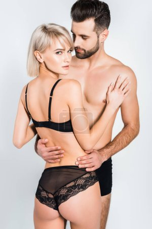 Photo for Attractive young couple in black underwear embracing isolated on grey - Royalty Free Image