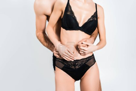 Photo for Cropped view of young man embracing woman in black lingerie isolated on grey - Royalty Free Image