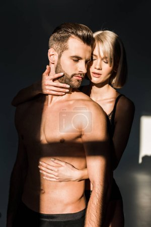 Photo for Sensual girlfriend hugging shirtless bearded boyfriend with shadows on torso - Royalty Free Image