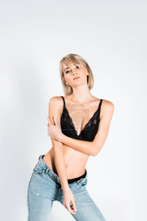 Photo for Beautiful sensual young woman posing in black lingerie and jeans isolated on grey - Royalty Free Image
