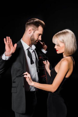 Photo for Elegant blonde woman undressing handsome man isolated on black - Royalty Free Image