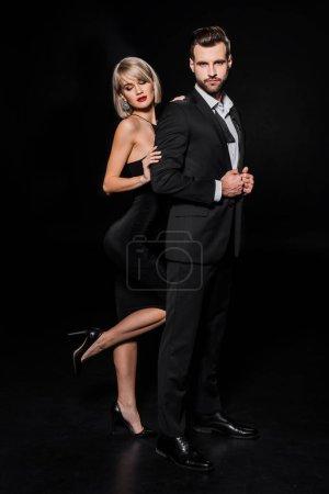 Photo pour Femme glamour jeune posant avec bel homme élégant sur fond noir - image libre de droit
