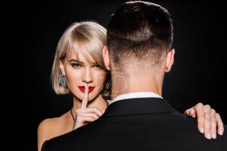Photo pour Belle femme blonde montrant le symbole du silence tout en se tenant avec petit ami isolé sur noir - image libre de droit