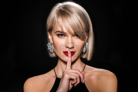 Photo for Beautiful glamour woman in earrings showing silence symbol, isolated on black - Royalty Free Image