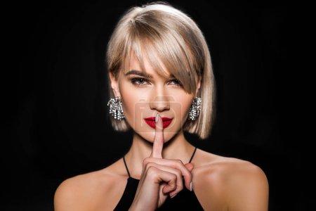 Photo pour Belle femme glamour dans des boucles d'oreilles montrant symbole de silence, isolé sur noir - image libre de droit