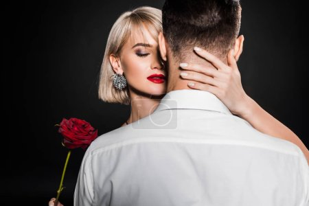 Photo for Passionate woman holding rose flower and hugging man, isolated on black - Royalty Free Image