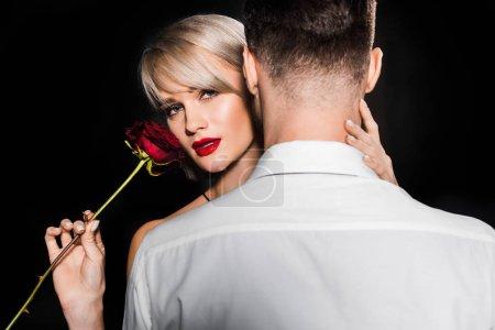 Photo pour Copine sensuelle tenue rouge rose fleur tout en étreignant son petit ami, isolé sur fond noir - image libre de droit