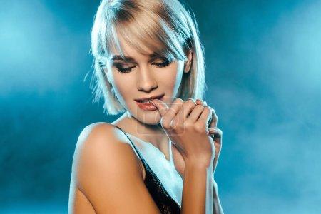 Photo pour Séduisante femme blonde posant sur fond bleu fumé - image libre de droit