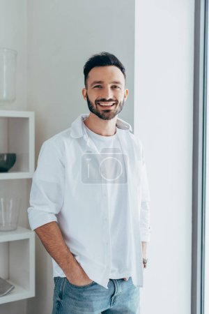 Photo for Laughing man in white shirt standing with hands in pockets - Royalty Free Image