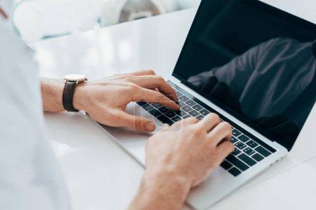 Photo pour Vue partielle de l'homme en montre-bracelet en tapant sur le clavier d'ordinateur portable - image libre de droit