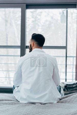 Photo pour Vue arrière du brunette homme en chemise blanche, assis sur le lit - image libre de droit