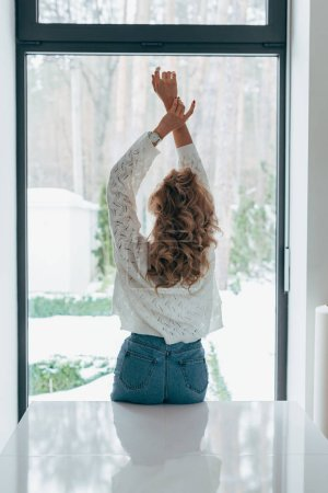 Back view of curly woman standing with hands up in front of window