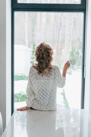Back view of curly girl standing in front of window with coffee cup