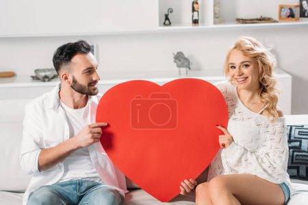 Photo for Smiling romantic couple holding big red heart - Royalty Free Image