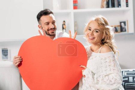 Photo pour Couple gai tenant coeur rouge et montrant des signes de paix - image libre de droit
