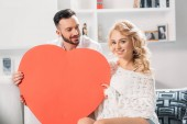 """Постер, картина, фотообои """"Счастливый романтическая пара, улыбаясь во время держит красное сердце"""""""
