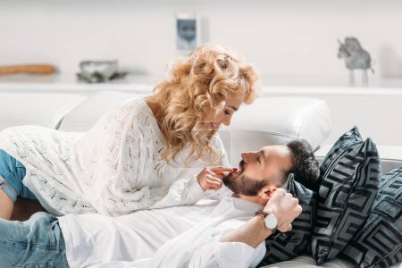 Photo for Charming curly woman lying on sofa with boyfriend - Royalty Free Image