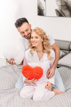 Photo for Happy couple sitting on bed and holding toy hearts - Royalty Free Image