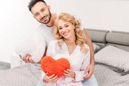 Photo pour Couple heureux holding coeurs jouet tout en étant assis sur le lit - image libre de droit