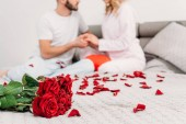 """Постер, картина, фотообои """"Частичный вид пара сидит на кровати с лепестками роз и взявшись за руки"""""""