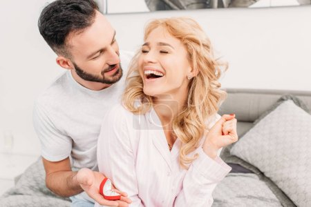 Photo for Brunette man proposing to laughing woman in bedroom - Royalty Free Image