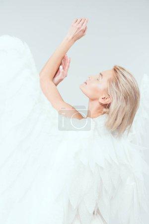 Photo pour Foyer sélectif de belle femme tendre avec des ailes d'ange geste avec les mains isolées sur blanc - image libre de droit