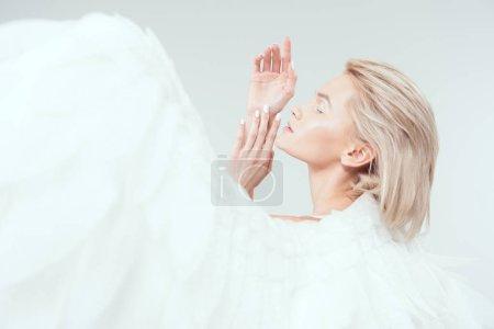 Photo pour Mise au point sélective de belle femme tendre avec des ailes d'ange gesticulant avec mains isolés sur blanc - image libre de droit