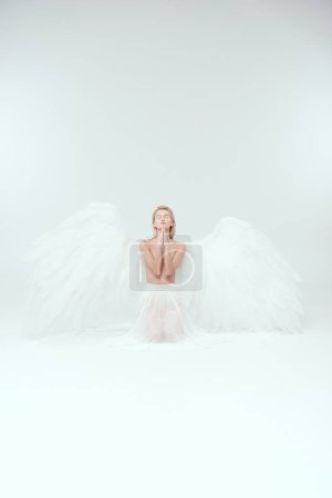 Photo for Beautiful woman with angel wings praying isolated on white with copy space - Royalty Free Image