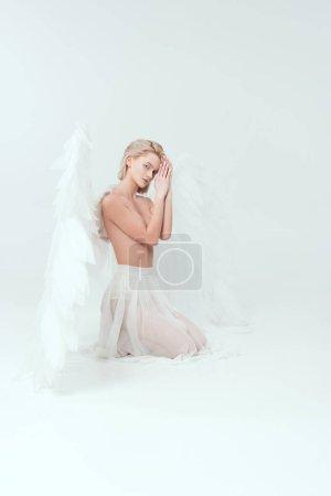Photo pour Belle femme avec des ailes d'ange regardant la caméra et posant isolé sur blanc - image libre de droit