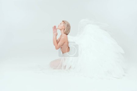 Photo for Beautiful tender woman with angel wings sitting and gesturing with hands isolated on white - Royalty Free Image
