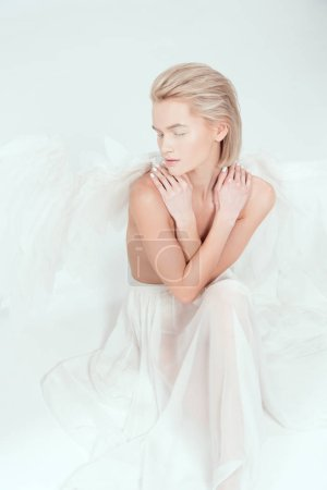 Photo for Beautiful woman with angel wings covering breasts and posing with eyes closed isolated on white - Royalty Free Image