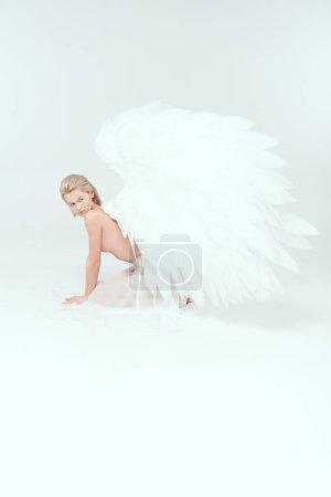 Photo pour Belle moitié nue jeune femme avec des ailes d'ange posant sur fond blanc - image libre de droit