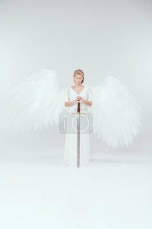 Photo pour Belle femme avec des ailes d'ange tenant épée et posant sur fond blanc - image libre de droit