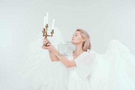 Foto de Hermosa mujer en traje de Ángel con alas que sostiene el candelabro con velas aislados en blanco - Imagen libre de derechos