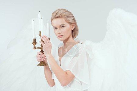 Foto de Hermosa mujer en traje de Ángel con alas sosteniendo candelabros con velas y mirando a cámara aislada en blanco - Imagen libre de derechos