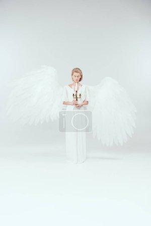 Photo pour Belle femme en costume d'ange avec des ailes et les yeux fermés tenant candélabre avec des bougies sur fond blanc - image libre de droit